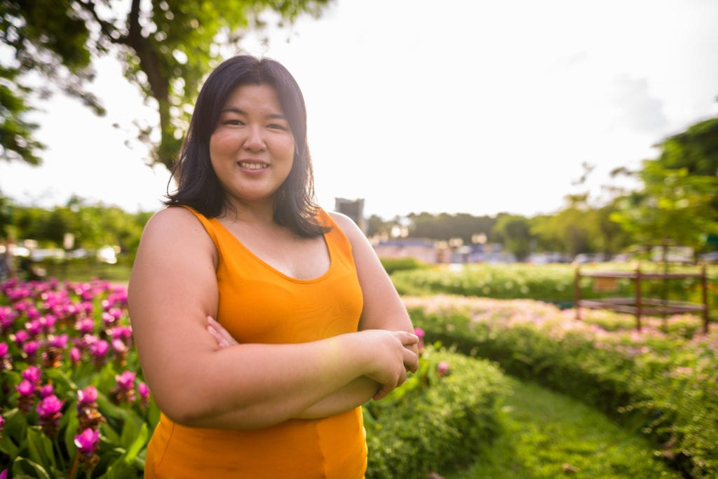 Beautiful overweight Asian woman with arms crossed in park